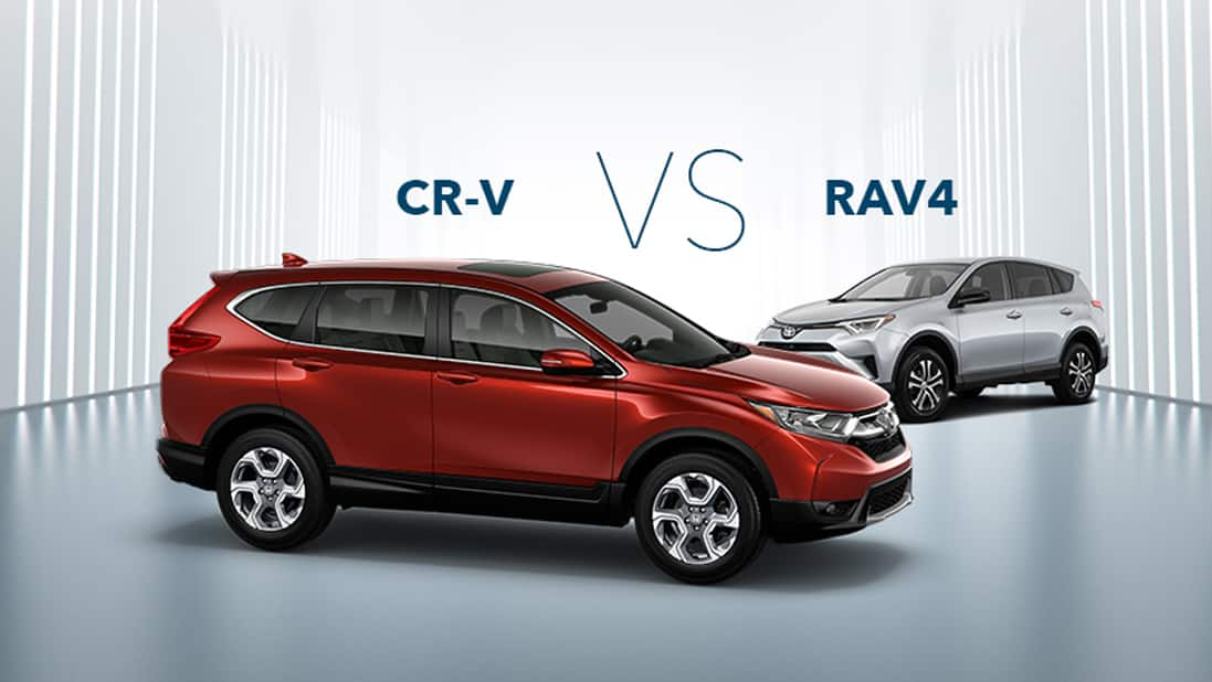 Front 3/4 passenger's side view of the 2019 Honda CR-V in Deep Scarlet Pearl parked in studio environment next to Toyota RAV4.