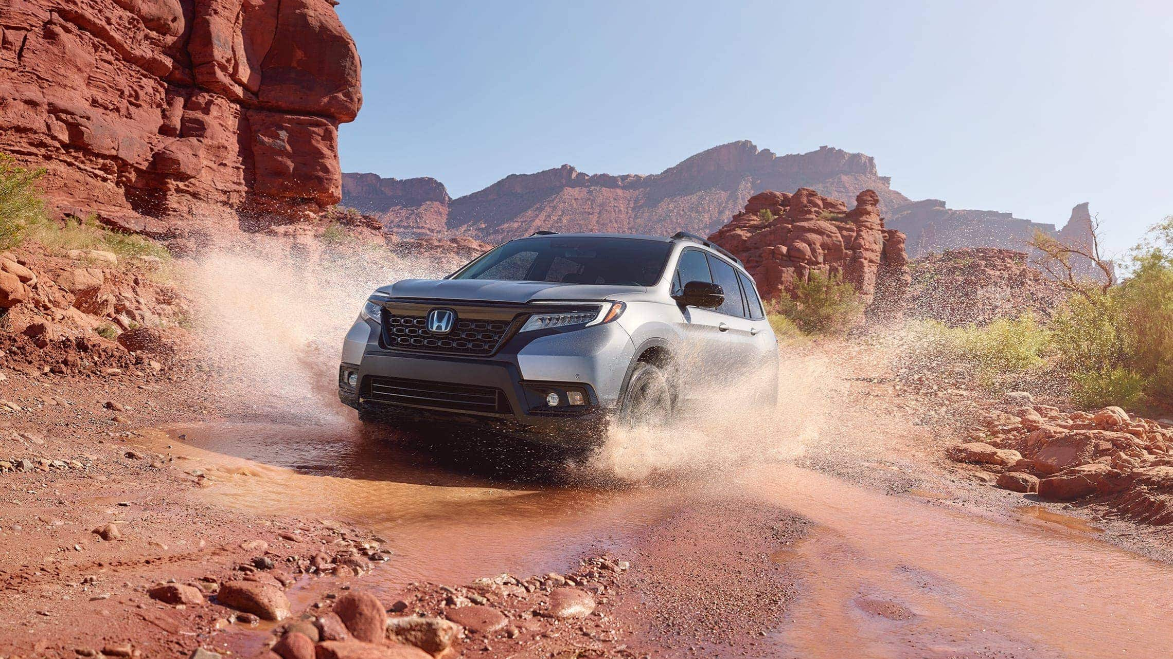 Driver-side front 3/4 view of 2019 Honda Passport Elite in Lunar Silver Metallic, demonstrating all-wheel drive and splashing through water on a rugged mountain road.