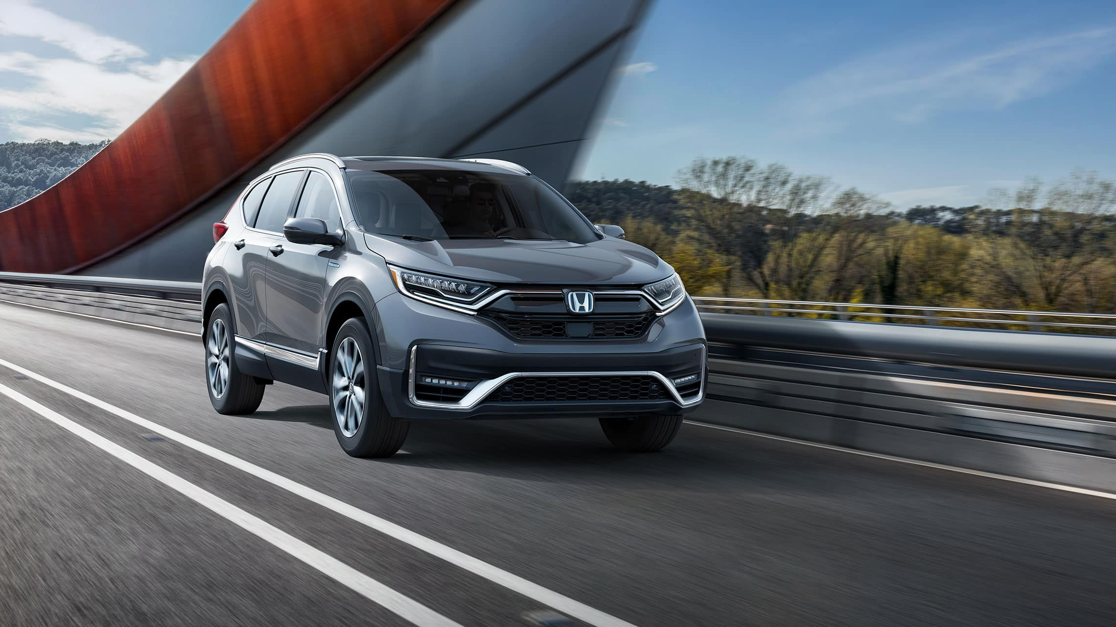 Front passenger-side view of the 2020 CR-V Hybrid Touring in Modern Steel Metallic, driving across a bridge.
