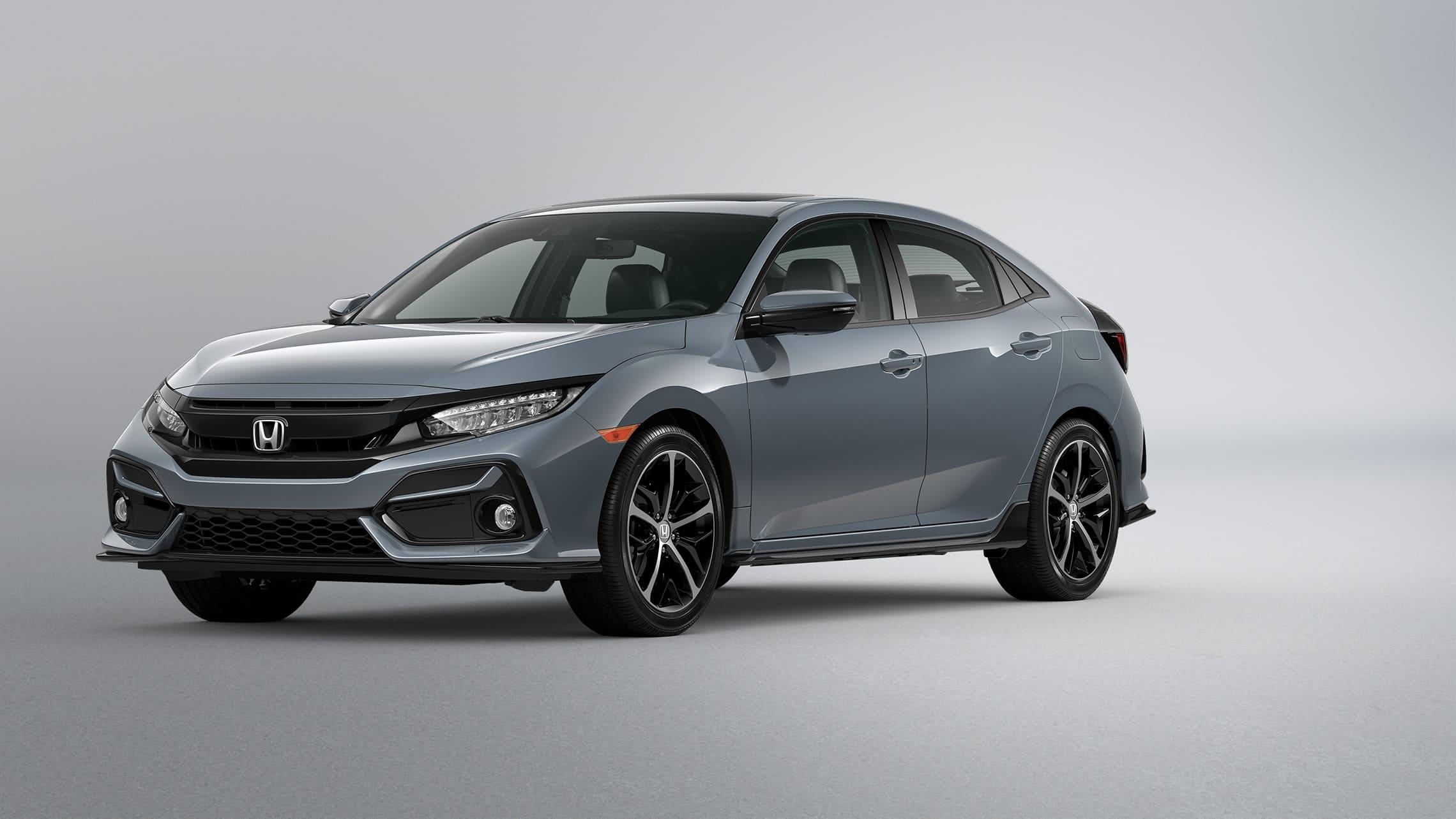 Vista frontal desde el lado del conductor del Honda CivicSportTouringHatchback2021 en Sonic Gray Pearl.