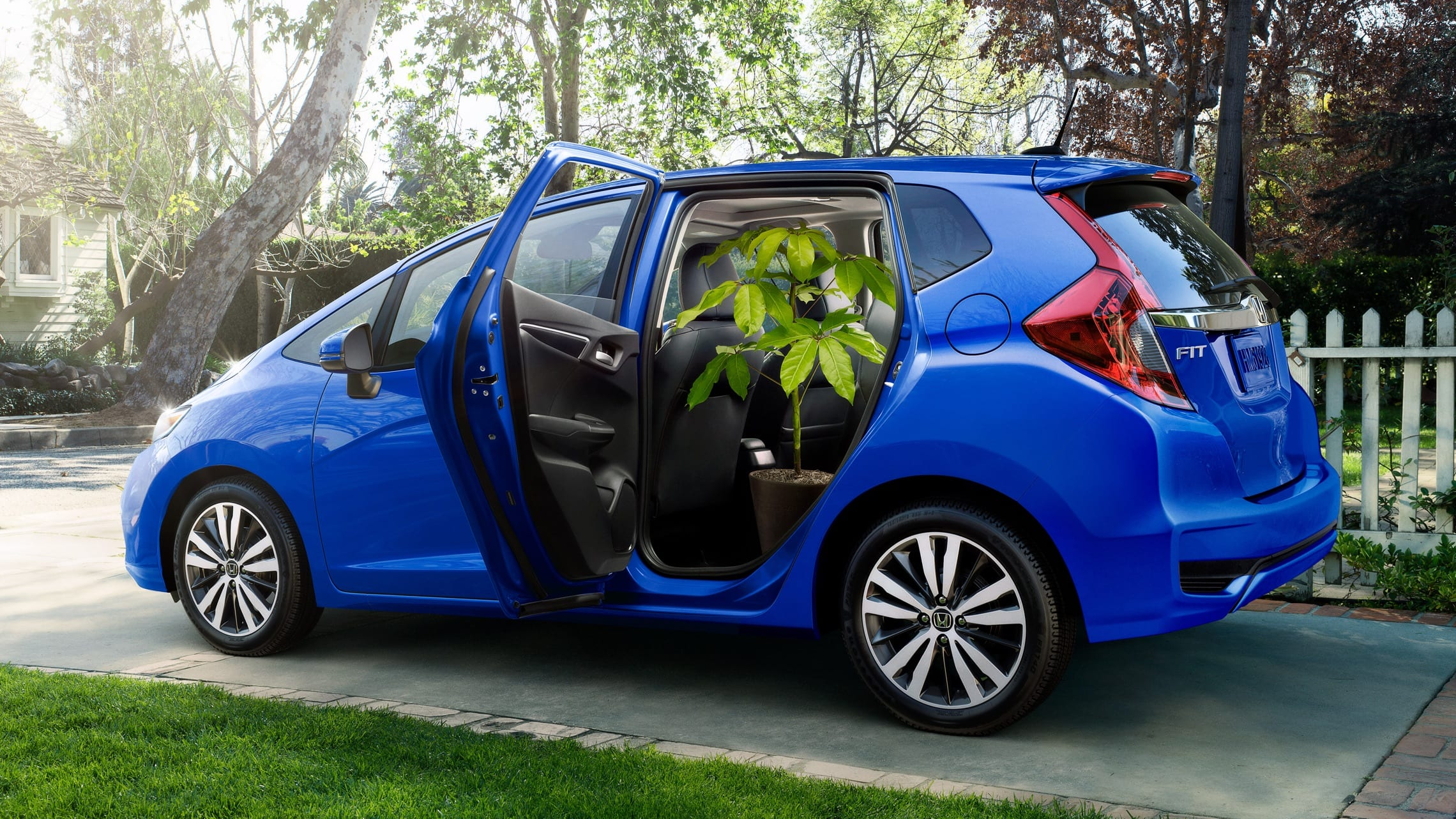 Rear passenger-side view of the 2020 Honda Fit EX-L in Aegean Blue Metallic with 2nd-row Magic Seat® folded up and houseplant in second row.