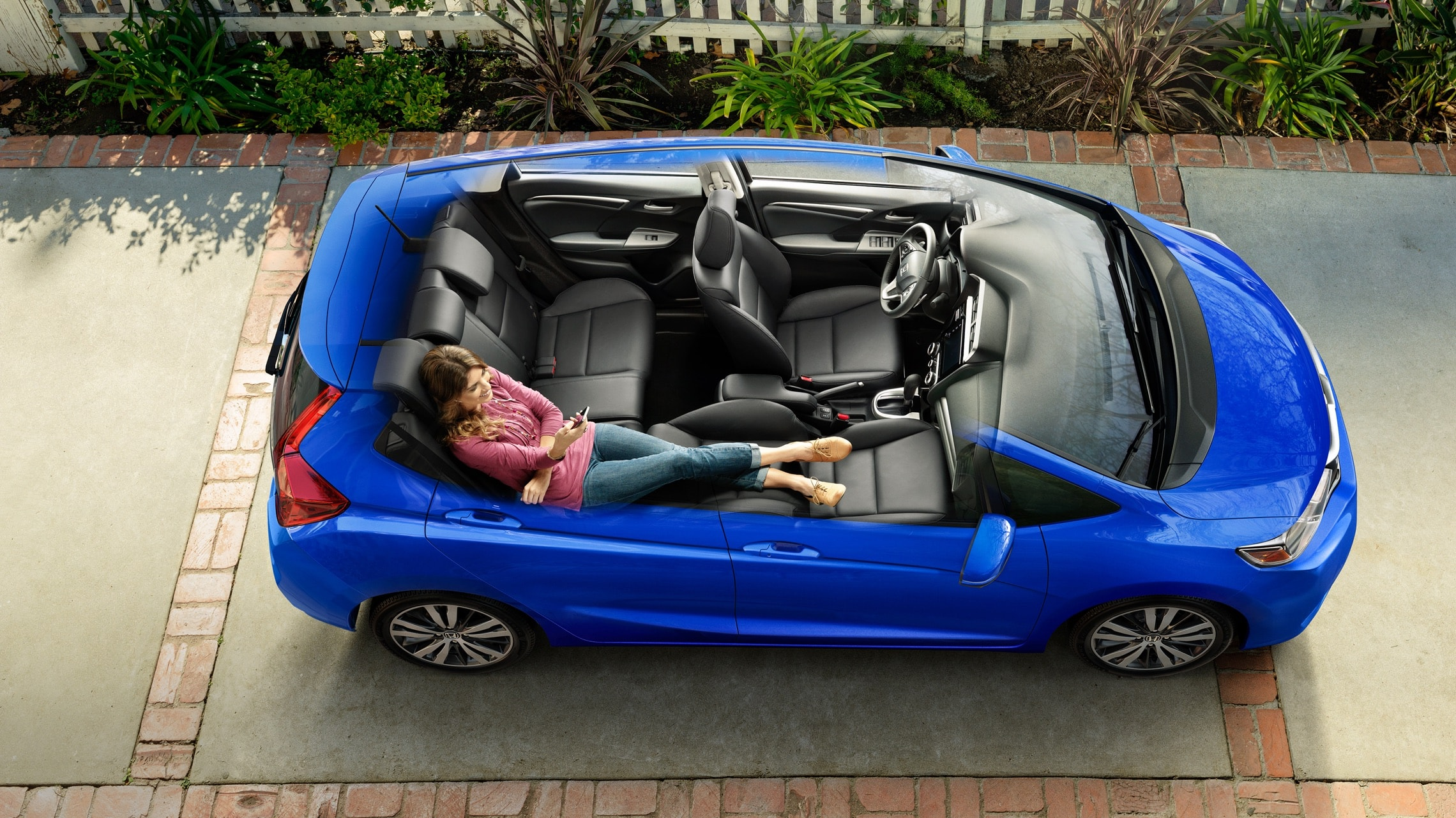 Overhead interior view of the 2020 Honda Fit EX-L in Aegean Blue Metallic with front passenger seat reclined fully back and 2nd-row Magic Seat® reclined.