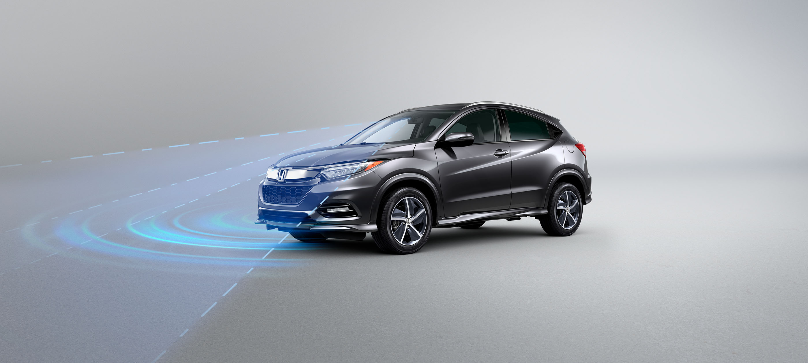 Front driver-side view of 2020 Honda HR-V Touring in Modern Steel Metallic with Honda Sensing® illustrated demonstration.