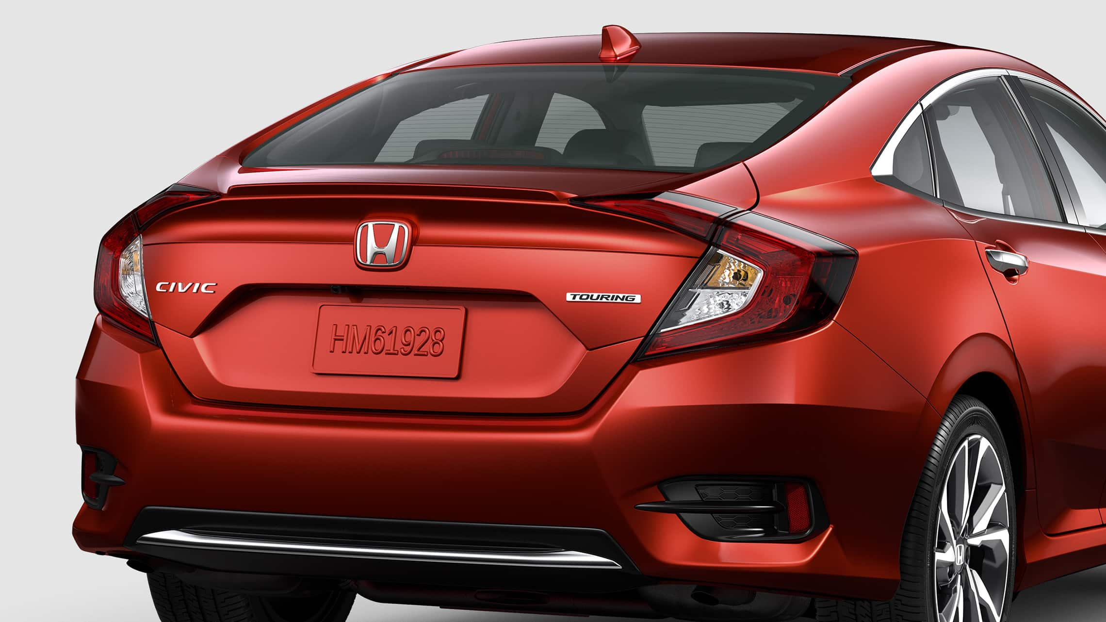 Rear passenger-side view of the 2021 Honda Civic Touring Sedan in Molten Lava Pearl.